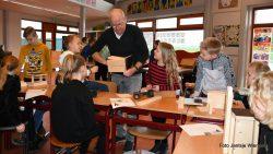 Pieter van der Ploeg helpt de kinderen met nestkastjes maken